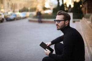 pensive troubled stylish man with notepad on street